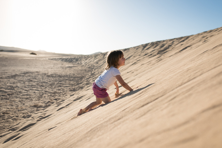 Courageous girl climbing up sand dunes Stock Photo