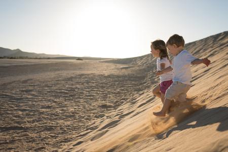 Children having fun running down the sand dune