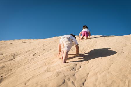 Kids having fun running on the sand dune