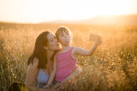 Humorous mother and daughter sticking out tongue together Stock Photo