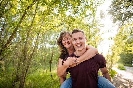 Happy caucasian mother enjoys a piggy back ride with son Stock Photo