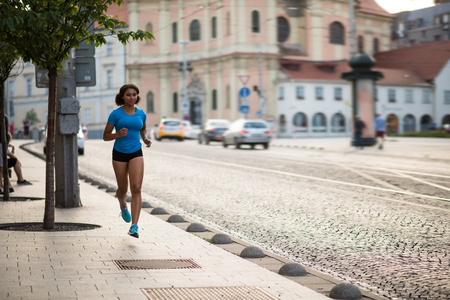 Young fitness woman running on sidewalk