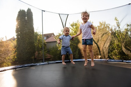 Siblings jumping together on trampoline