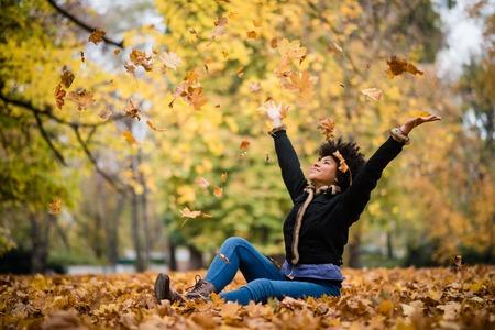 Smiling teen girl throwing leaves in the air