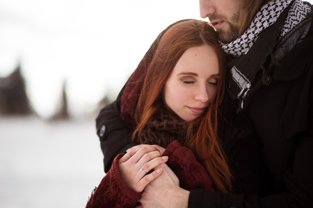 Redhead woman feels warmth of her boyfriend