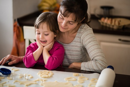 Mother and smiling daughter - baking cookies together