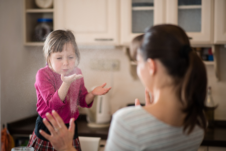 Daughter blowing flour on mother during baking