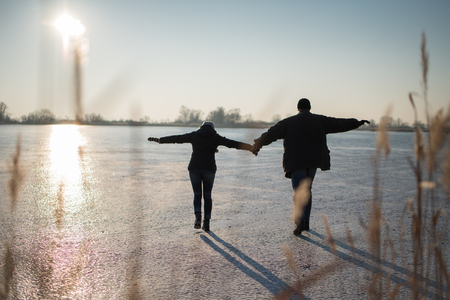 Couple carefully stepping together on frozen lake Foto de archivo - 113275608
