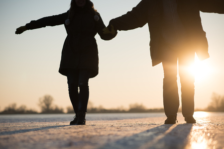 Romantic couple carefully stepping on frozen ice. Stock Photo