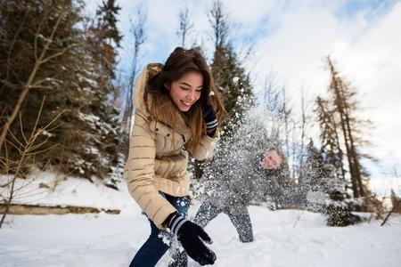 Couple enthousiaste se réjouissant à l'extérieur en hiver