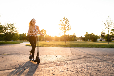 Fun loving woman rides kick scooter in park Stock Photo