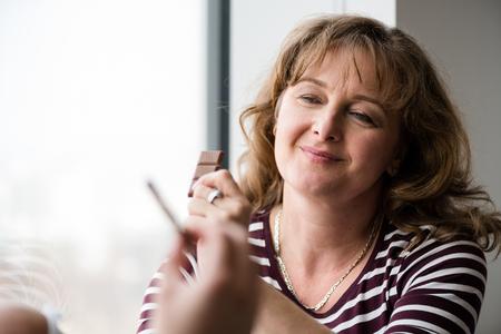 Smiling beautiful mature woman holding chocolate bar Stockfoto