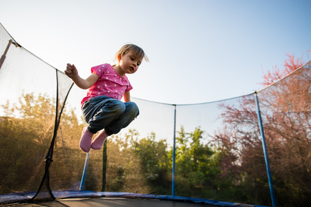 Young kid jumping on trampoline bed