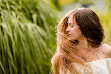 Teen woman with eyes closed swaying hair