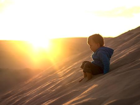 Adorable little boy sliding down the desert dune Imagens