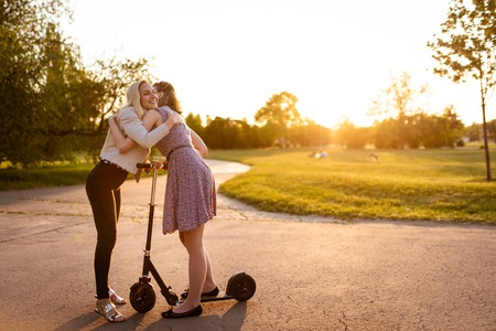 Young women embrace each other outside