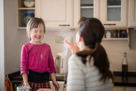 Mother blowing flour on daughter during baking Stock Photo