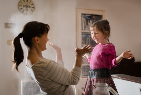 Mother with daughter having fun by cooking