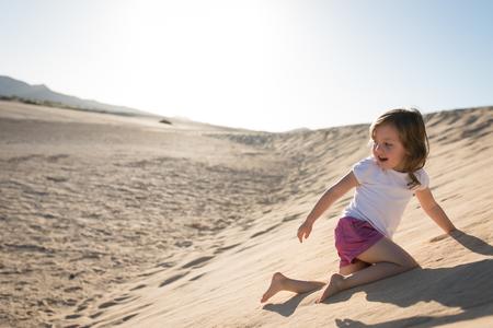 Little girl climbing up sand dunes