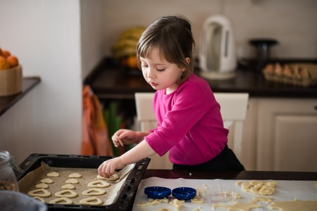 Little girl gives cookies on baking pan Stockfoto