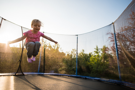 Little adorable girl playing on trampoline 写真素材