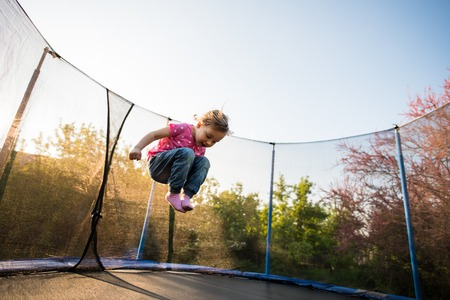 Child jumping high in the air on a trampoline