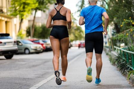 Couple jogging on sidewalk, rear shot. 版權商用圖片