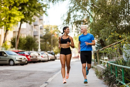Active joggers training outdoors on sidewalk