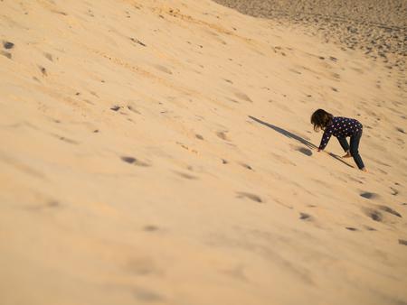Little girl climbing the sandy desert dune Banque d'images - 119398219