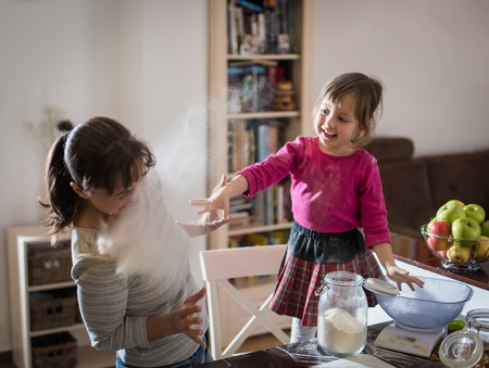 Cute daughter throwing flour on mother during baking Stock Photo