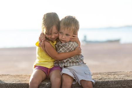 Fratello e sorella seduti in riva al lago che si abbracciano Archivio Fotografico