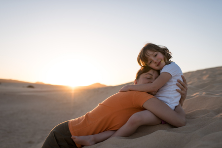 Mother laying on sand dune and hugging with her daughter