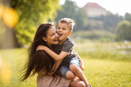 Laughing young mother with kid on her lap
