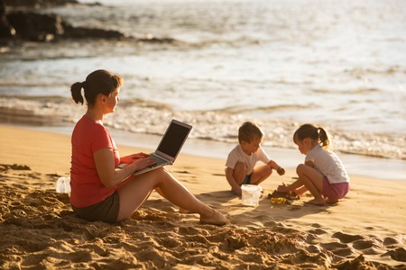 Mother teleworking as kids play in front of her