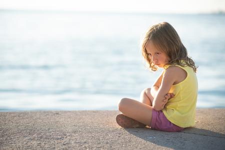 Sad child sitting at the lake edge