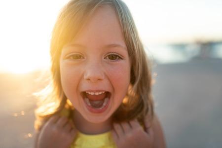 Little girl bursting out in laugher, portrait shot.