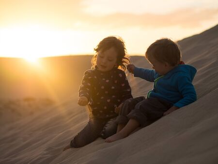 Kids sitting on dune playing with sand particles Stockfoto