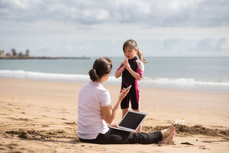 Daughter begs young mother to play with her at the beach Foto de archivo