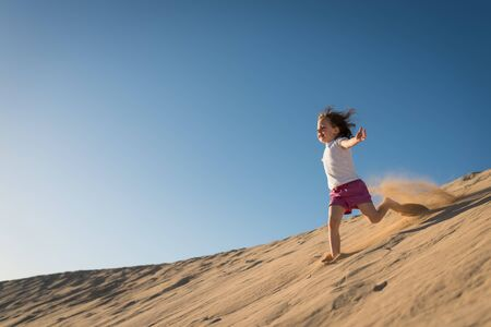Child running down sand dune