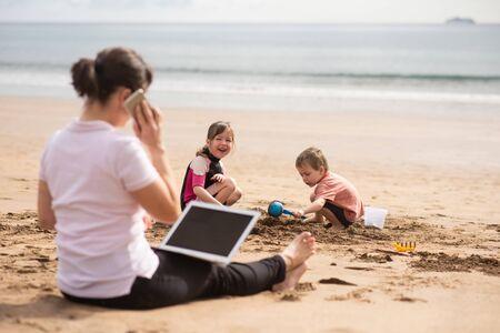 Fleißige Mutter, die Arbeit und Leben in Einklang bringt und mit Kunden über Telefon spricht. Standard-Bild