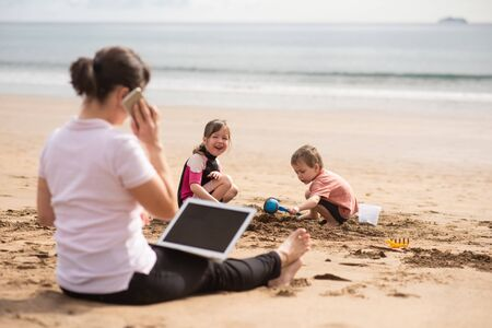 Hardworking mother balancing work-life, talking to clients over call. Stockfoto