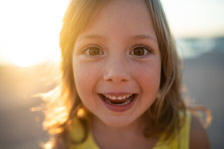 Portrait shot of cheerful little girl during sunset