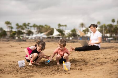 Children playing with beach toys while mother balances work-life Stockfoto