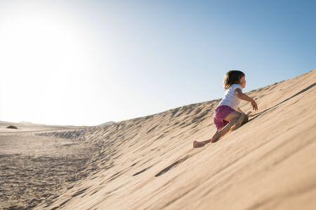 Courageous little girl climbing sand dune under the blue sky