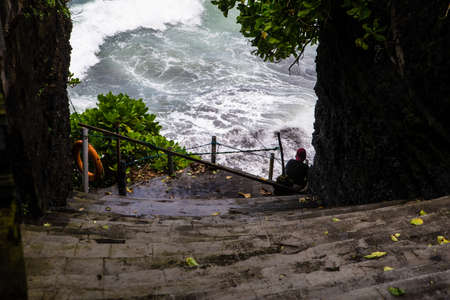 People enjoy their free time around the Tanah Lot water temple in Bali, one of the most popular temple in Indonesia. The temples are full of tourists all year. The Balinese temples are arranged according to the physical and spiritual realm of Balinese peo Editorial