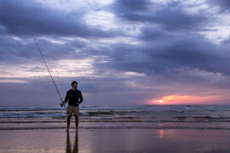 A young man fishing in the open sea along the Atlantic Ocean shoreline at Costa da Caparica in Lisbon, Portugal. Attractive guy holding the fishing rod at sunset on the beach. Hobby lifestyle