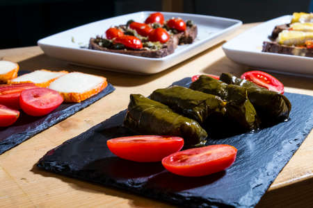 Dolma, delicious Casucasian and Turkish cuisine, vine leaves stuffed with minced meat and rice. Italian bruschetta with tomatoes and cheese in background. Imagens