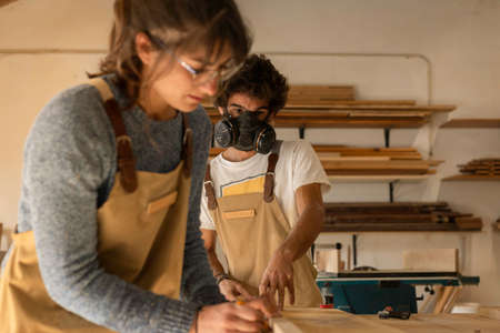 A young man working as carpenter in his wood workshop. Wood worker designing and handcrafting new house furniture using a piece of timber and wearing a full face mask for the dust