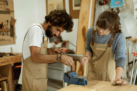 A young couple of carpenter working together in a small wood laboratory using a drill machine for timber. Couple crafting new home furniture in a carpentry workshop. young entrepreneurs concept