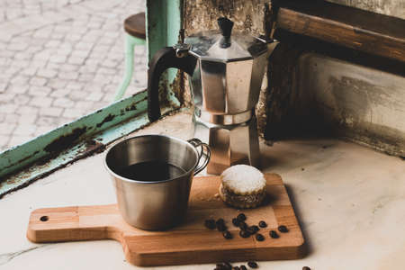 Italian black coffee in a cup with coffee beans and a handmade cookie with sugar and a Moka pot behind. Everything in vintage brown background close to the window. Healthy Breakfast.